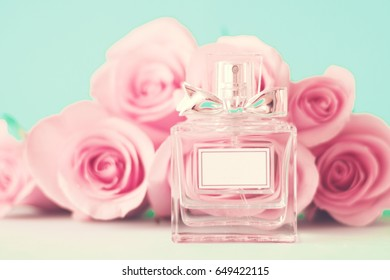 Vintage perfume bottle and roses over mint background