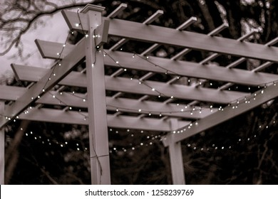 Vintage pergola with Christmas lights draped over it on a cool winter evening