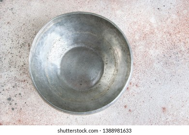 Vintage pewter bowl on a concrete background. Copy space for text.