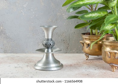 Vintage pewter candlestick and green plants in brass flower pots on concrete background. Copy space for text.