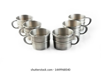 Vintage pewter cups on white background. Copy space for text.