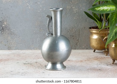Vintage pewter jug and green plants in brass flower pots on concrete background. Copy space for text.