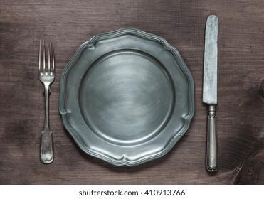 Vintage pewter plate, fork and knife on old dark wooden board