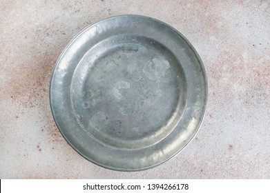 Vintage pewter plate on a concrete background. Copy space for text.