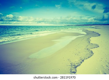 Vintage photo of beautiful beach landscape with cloudy sky and sea with waves. Baltic sea coast near Gdansk in Poland.