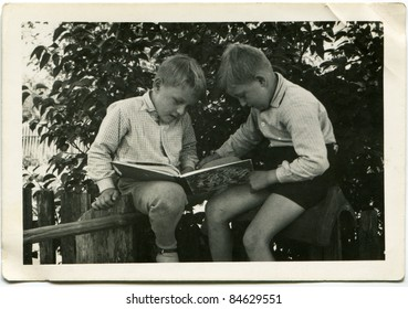 Vintage photo of brothers reading a book (fifties)