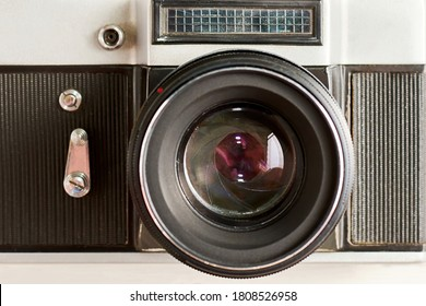 Vintage photo camera with optical lens and aperture blades, front view as icon. Old retro devices backgrounds