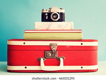 Vintage photo camera over books and antique suitcase