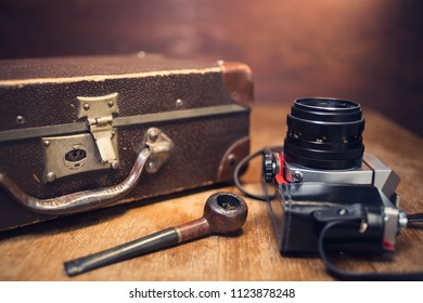 Vintage photo camera, pipe and suitcase on table.