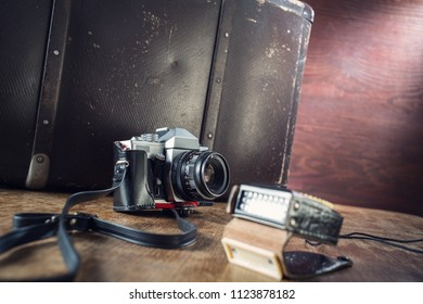 Vintage photo camera and suitcase on table.