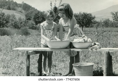 Vintage photo of children doing laundry outdoor (fifties)