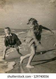Vintage photo of children running on beach (visible motion blur) - fifties