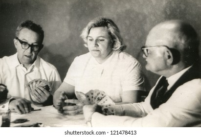 Vintage photo of elderly man playing cards with his daughter and son-in-law (sixties)