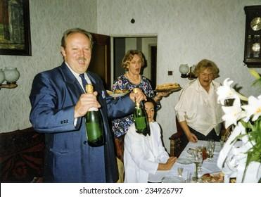 Vintage photo of family celebrating elderly couple's wedding anniversary, eighties