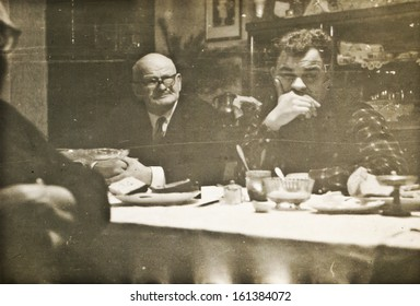 Vintage photo of father and son during family dinner (sixties)