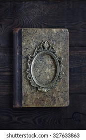 Vintage photo frame on the old book on a dark background
