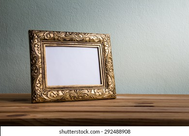 Vintage photo frame on wooden table over grunge background