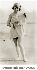 Vintage photo of a Girl On Beach Covering Self With Newspaper