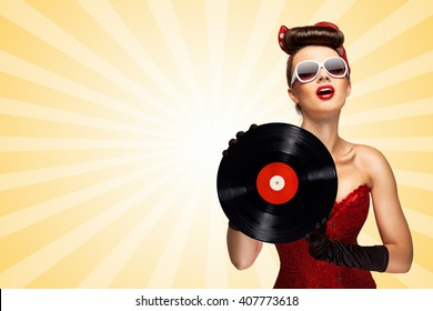 Vintage photo of glamorous pinup girl wearing long gloves and dressed in a red sexy corset, holding LP vinyl record on colorful abstract cartoon style background.