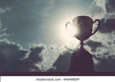 Vintage photo of Golden trophy with dark sky background with copy space ready for your design , Conception of victory in the competition.