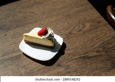Vintage Photo of Good morning vacation time and enjoy holiday with New York style Cheesecake with fresh strawberry on white plate decorated wood table and have sunlight