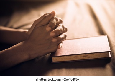 Vintage photo of hand with Bible praying , Hands folded in prayer on a Holy Bible , Spirituality and Religion Concept