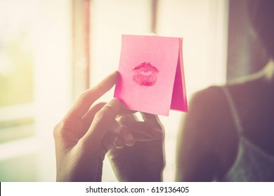 Vintage photo of hands holding a paper message with the lipstick trace of a kiss on mirror , Sexy girl Red lips kiss on note paper in the morning light. romantic message from couple
