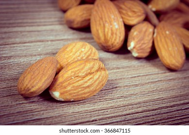 Vintage photo, Heap of fresh healthy almonds on wooden background, concept for healthy nutrition