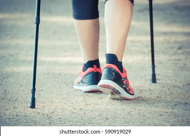 Vintage photo, Legs of elderly senior woman in sporty shoes practicing nordic walking, healthy lifestyles in old age