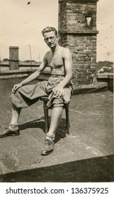 Vintage photo of man tanning on the roof, forties