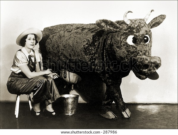 Vintage photo of a Milkmaid Sitting Next To Stuffed Cow