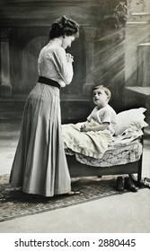 Vintage photo of a mother gazing at her young son in bed.