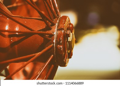 Vintage photo of an old red metal car wheel showing metal spokes, with space for text. Can be used as a background for Fathers Day.