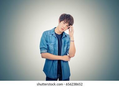 The vintage photo portrait of an Asian boy in denims jacket feeling headache.
