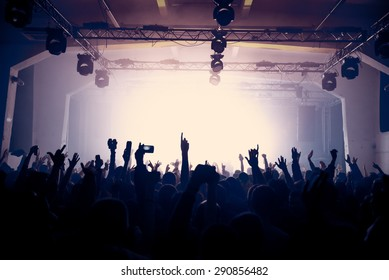 Vintage photo of a raised hands silhouettes at the rock concert, clubbing or celebrating New Year's eve. Active night life concept, higher ISO image, selective focus. No recognizable people.