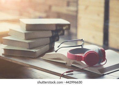 Vintage photo of Red headphone on book in cafe or library,morning light.