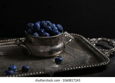 Vintage photo set up with fresh blueberries covered with water drops in a silver vintage bowl on a silver plate with lace and water.  Summer Berries.