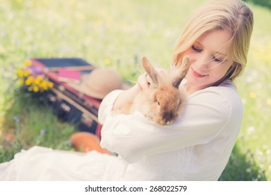 Vintage photo of teenager girl with bunny in the nature, selective focus and creative vintage editing with slightly noise