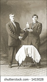 Vintage photo of Two Men Shaking Hands Holding Bottle Of Alcohol