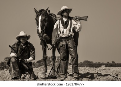 Vintage photo, of two men wearing a cowboy outfit with a horse and a gun held in the hand.