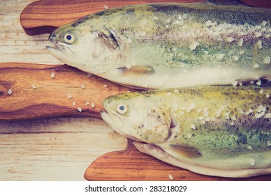 Vintage photo of two rainbow trouts on a cutting board. studio shot