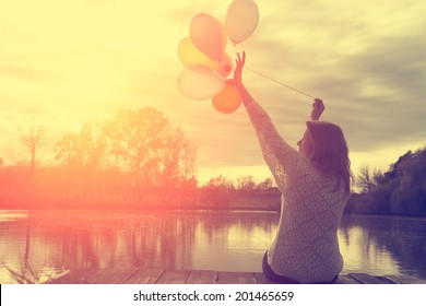 Vintage photo of woman having fun with balloons in sunset