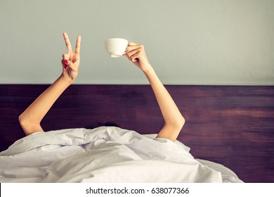 Vintage photo of Woman showing the funny sign and holding cup behind blanket in the bed , two woman hands sticking out from the blanket