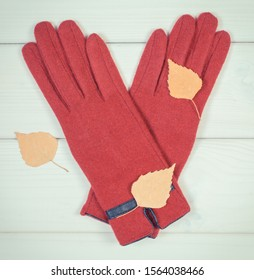 Vintage photo, Woolen gloves for woman and autumnal leaves on white boards, warm clothing for autumn or winter