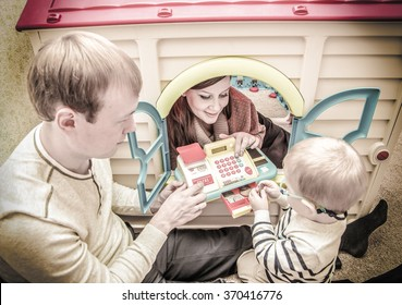 Vintage photo of young family playing with toy cash register in children playroom