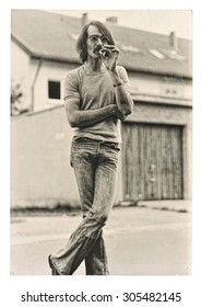 Vintage photo from young fashion smoking man wearing typical 1970s clothing. Retro picture with original film grain and scratches.