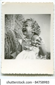 Vintage photo of young girl with doll (fifties)
