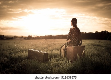 Vintage photo of young pregnant female with two luggage looking desperate in the sunset in meadow. Moment from the movie or fairy tail motive. Color toned image. Retro filtered.