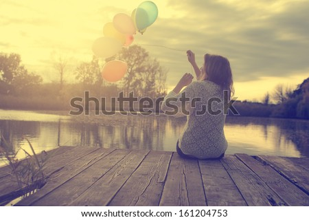 Vintage photo of young woman with balloons