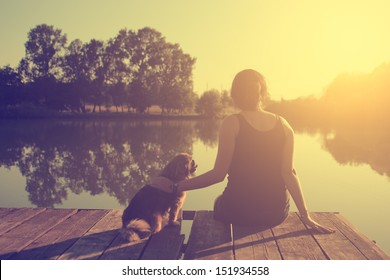 Vintage photo of young woman relaxing with her dog at the lake in sunset